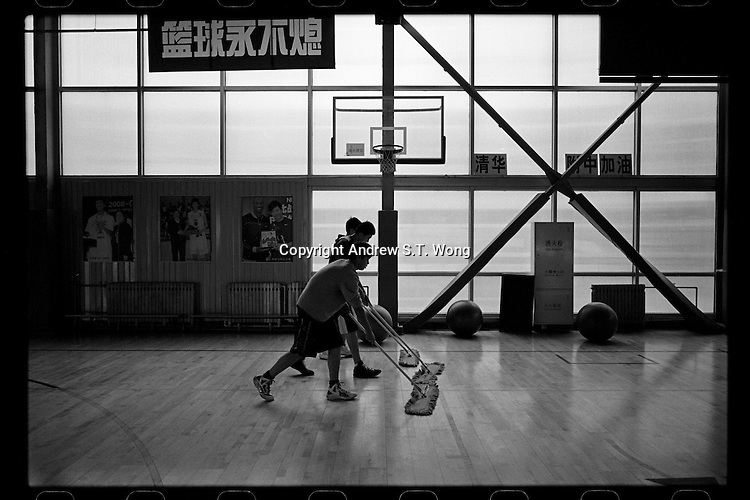 Young players of Tsinghua University Affiliated Middle School basketball team mop the court before a training session at the basketball hall of Tsinghua University Affiliated Middle School in Beijing, January 2012.