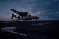 An E-2C Hawkeye recovers aboard USS Carl Vinson as night falls in the Indian Ocean.