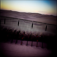 The sun sets at the Mexico border fence near San Diego in Southern California.
