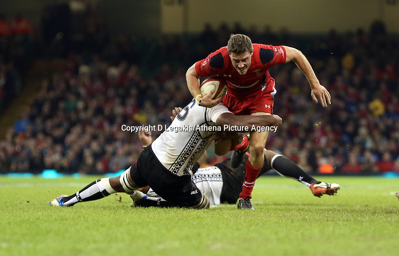 Pictured: Rhys Priestland of Wales (R) brought down by Dominiko Waqaniburotu of Fiji (L). Saturday 15 November 2014<br /> Re: Dove Men Series rugby, Wales v Fiji at the Millennium Stadium, Cardiff, south Wales, UK.