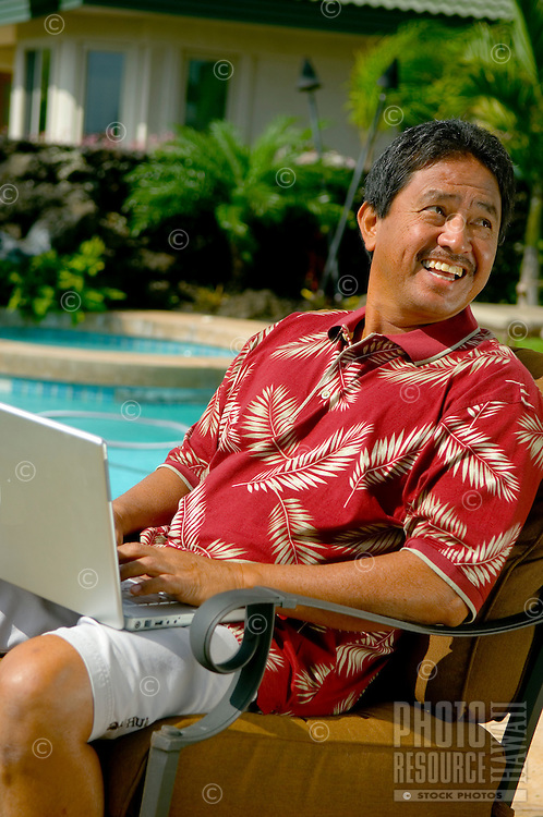 Local man on laptop computer near pool outdoors.