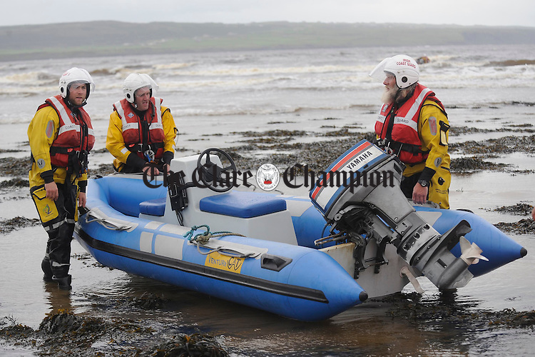 Members of the Doolin coastguard work to recover a rib which was set loose at the pier and later grounded on rocks by strong gales in Liscannor on Tuesday night. Photograph by John Kelly.