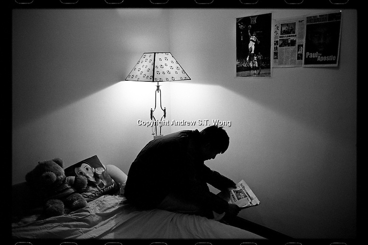 Basketball player Lu Chenyang of Huazhong Shida First Affiliated High School in Wuhan, Hubei province, reads a newspaper underneath a NBA poster at his bedroom after returning home from training at school December 2011.