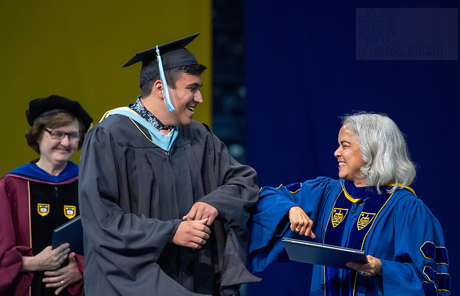 July 10, 2021; 2021 Provost Marie Lynn Miranda elbow bumps a graduate as he receives his diploma during the Commencement Ceremony of the University of Notre Dame's Alliance for Catholic Education (ACE) in the Purcell Pavilion of the Joyce Center. (Photo by Barbara Johnston/University of Notre Dame)