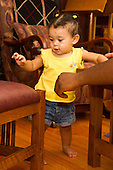 "MR / Schenectady, NY. Infant in pre-walking stage (girl, 10 months, African American & Caucasian) exhibiting 10-month-old human development milestone behavior as she holds onto furniture at her level to ""cruise"" in living room. She is hesitant so her father holds his hand out for support, if needed. MR: Dal4. ID: AL-HD. © Ellen B. Senisi"