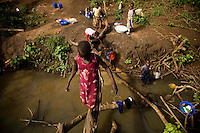 Children washing clothes and cooking pots in the creek at Nyori refugee camp in South Sudan. The drinking water in the camp comes from boreholes drilled by MSF and UNHCR.