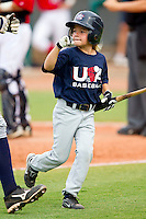 The bat girl fist bumps with an AABC player during the game against Babe Ruth at the 2011 Tournament of Stars at the USA Baseball National Training Center on June 26, 2011 in Cary, North Carolina.  Babe Ruth defeated AABC 3-2 in the Gold Medal game. (Brian Westerholt/Four Seam Images)