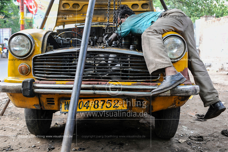 INDIA West Bengal, Kolkata, open garage in Elgin Road , open air repair of a HM Ambassador yellow cab, the car is still produced new at Hindmotor factory after license of Oxford Morris  / INDIEN Westbengalen Kalkutta, offene Kfz Werkstatt in der Elgin Road , Reparatur eines Ambassador Taxi , der HM Ambassador laeuft heute noch neu nach Vorlage des Oxford Morris bei HM Hindustan Motors vom Band