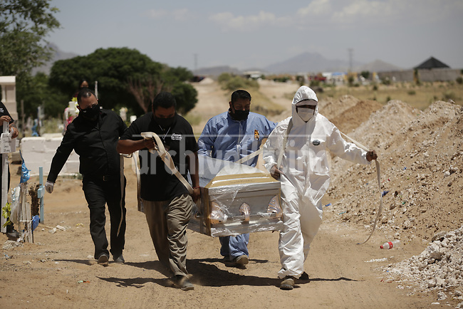 Burial of a  Covid 19 pandemic victim in the cementery of  Ciudad Juarez, on the Mexican border with the USA. Amidst the never ending violence of this city, corona virus is taking a high death toll.