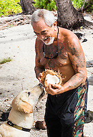 A local Hawaiian man cracks open a coconut for a dog to eat, Honaunau, Hawai'i Island.