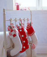 Red and white handmade Christmas stockings filled with small gifts and sweets