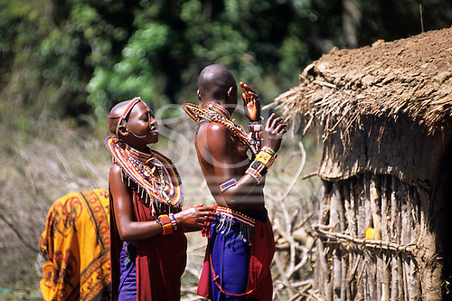 Lolgorian, Kenya. Siria Maasai Manyatta; two smiling girls with traditional bead neck adornments outside a thatched house.