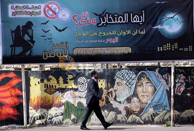 """A Palestinian man walks past a banner in Gaza City announcing the launch of a campaign against collaborating with Israel on March 13, 2013, as the ruling Hamas launches a month-long campaign to encourage """"collaborators"""" with Israel to repent. Photo by Ashraf Amra"""