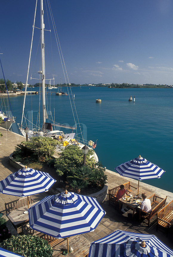 café, Bermuda, St. George's Parish, Wharf's Tavern outdoor café with blue and white umbrellas overlooking the aqua blue water of St. George's Harbor in St George in Bermuda.