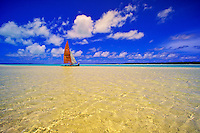Catamaran sailing off an uninhabited island in Aitutaki Lagoon, Cook Islands, in the South Pacific.