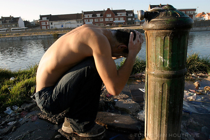 A refugee washes himself in public in Calais, France on Nov. 05, 2003.  Officials estimate that there are 150-300 refugees living in the streets of Calais.