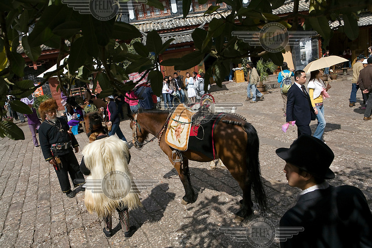 Tourists and Nakhi (Naxi) tour guides in the old city of Lijiang, a centre of Nakhi culture which is a UNESCO World Heritage Site.