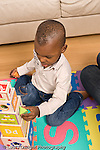2 year old toddler boy playing with stack of shape sorting blocks African American vertical