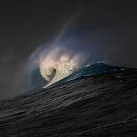 At wintertime, a rainbow blends into the spray of a breaking wave at Waimea Bay on the North Shore of O'ahu.