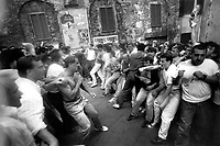 © Francesco Cito / Panos Pictures..Siena, Tuscany, Italy. The Palio. ..Residents of rival contradas (city districts) square up for a fight on the day of the race...Twice each summer, the Piazza del Campo in the medieval Tuscan town of Siena is transformed into a dirt racetrack for Il Palio, the most passionately contested horse race in the world. The race, which lasts just 90 seconds, has become intrinsic to the town's heritage since it was first run in 1597.