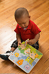 12 month old baby boy playing with wooden puzzle holding peg with pincer grasp