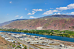 Columbia River at Wenatchee Confluence as seen from the mountainside gardens of Ohme Gardens.  This is the confluence of the Columbia River and the Wenatchee River.Fruit packing plants in the foreground.  Orchards and farming on far side of river.
