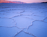 Death Valley National Park, CA<br /> Sunrise on the distant Panamint range and Grapvine mountains with Badwater's polygon salt patterns in the foreground