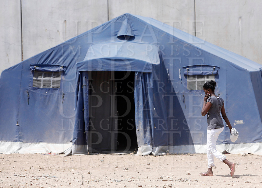 Una donna nella tendopoli allestita per i migranti presso la stazione Tiburtina a Roma, 16 giugno 2015.<br /> A woman walks in the tent camp set up near the Tiburtina railway station in Rome, 15 June 2015. Italy is facing a huge flow of migrants brought to Sicily after rescue at sea, many of whom are trying to join their relatives in northern Europe. <br /> UPDATE IMAGES PRESS/Riccardo De Luca