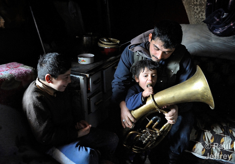 Milan Pesic gets help from one of his children as he practices his french horn inside his home in a Roma settlement in Belgrade, Serbia, in February 2012. Pesic plays in a Roma band. The families that live here, many of whom survive from recycling cardboard and other materials, are under constant threat of eviction in order to make way for new high-rise office buildings. Note: Pesic and other residents of this settlement were forcibly evicted in April 2012, two months after this photo. Many, including Pesic and his family, were relocated in metal shipping containers at the edge of the city..