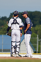 Princeton Rays pitching coach Jim Paduch (14) talks with catcher Roberto Alvarez (13) in a mound visit during the first game of a doubleheader against the Johnson City Cardinals on August 17, 2018 at Hunnicutt Field in Princeton, Virginia.  Johnson City defeated Princeton 6-4.  (Mike Janes/Four Seam Images)