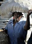 A woman carries a bag of produce on her head as she walks along a street in Port-au-Prince, Haiti.
