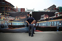 "CHINA. Beijing. Men peer through a fence, trying to catch a glimpse of the new Qianmen shopping district. In recent years construction has boomed in Beijing as a result of the country's widespread economic growth and the awarding of the 2008 Summer Olympics to the city. For Beijing's residents however, it seems as their city is continually under construction with old neighborhoods regularly being razed and new apartments, office blocks and sports venues appearing in their place. A new Beijing has been promised to the people to act as a showcase to the world for the 'new' China. Beijing's residents have been waiting for this promised change for years and are still waiting, asking the question ""Where's the new Beijing?!"". 2008."