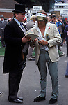 Royal Ascot, traditional and non traditional attire, two men share a Race card.  Berkshire England.  The English Season published by Pavilon Books 1987. Page 91R