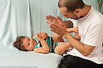 Infant development 12 month old baby boy interaction clapping hands game with father