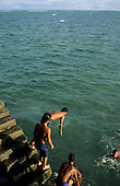 Salvador, Bahia, Brazil. Group of boys diving into the emerald sea from the harbour steps.