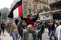 Protesters carrying an Egyptian flag march through the streets of central Cairo amidst tear gas fired by the police. Continued anti-government protests take place in Cairo calling for President Mubarak to stand down. After dissolving the government, Mubarak still refuses to step down from power.