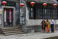 Suzhou, Jiangsu, China.  Tourists with a Selfie Stick Hurrying along a Sidewalk in Tongli Ancient Town near Suzhou.