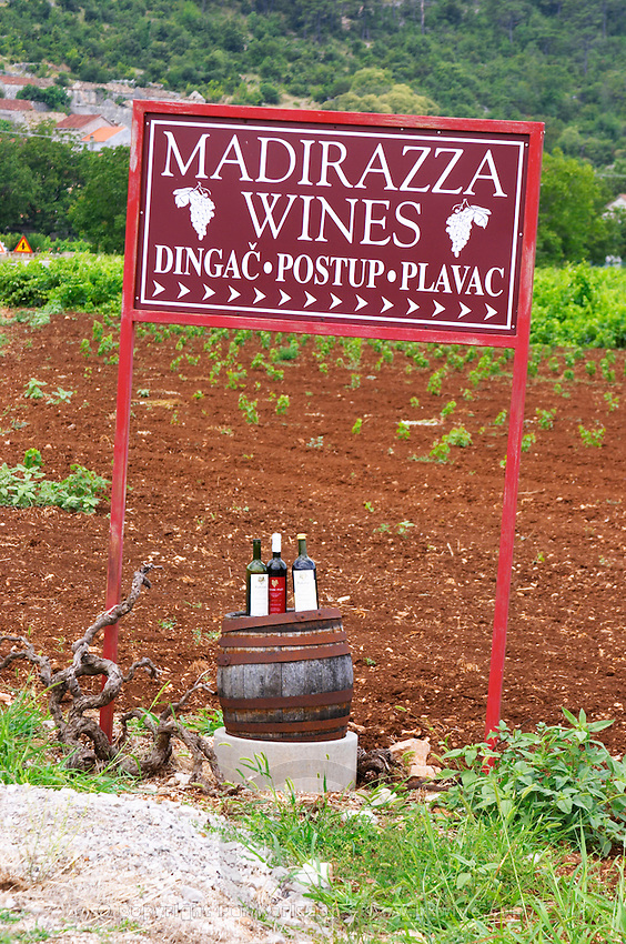 Sign saying Madirazza Wines, Dingac, Portup, Plavac. Bottles standing on a barrel, vineyard in the background. Potmje village, Dingac wine region, Peljesac peninsula. Dingac village and region. Peljesac peninsula. Dalmatian Coast, Croatia, Europe.
