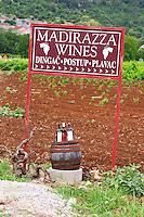 Sign saying Madirazza Wines, Dingac, Portup, Plavac. Bottles standing on a barrel, vineyard in the background. Potmje village, Dingac wine region, Peljesac peninsula. Dingac village and region. Peljesac peninsula. Dalmatian Coast, Croatia, Europe.