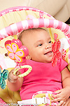 5 month old baby girl smiling in infant seat grasping hanging toy looking to side