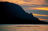 An outrigger canoe team paddles against a beautiful sunset at Makana point, Kauai.