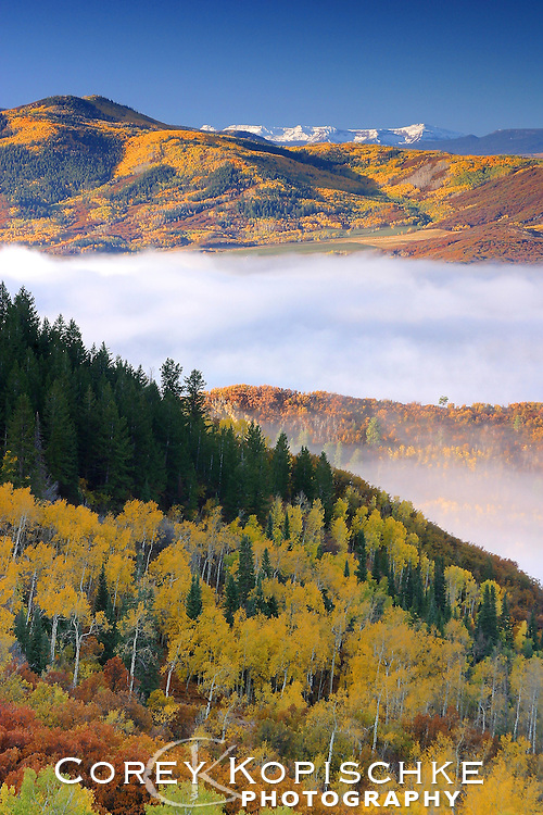 A fresh snowfall covers the distant Flat Tops while the morning fog burns off of Lake Catamount during peak fall foliage.