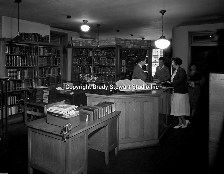 Pittsburgh PA: Students checking-out books at the Duquesne University library.<br />