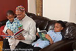 father at home reading book to 3 year old son with 8 year old son reading to himself in the background horizontal