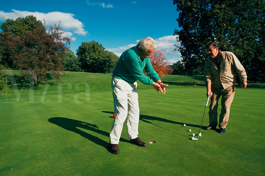 Golf pro giving lesson to a player.