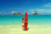 Girl with surfboard looking out to Mokulua Islands, off Lanikai, Kailua, Oahu