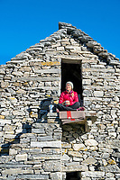 A woman drinking coffee at the Capanna Alpe Spluga, while hiking the Via Alta Via Maggia, a difficult week long trek from Locarno to Broglio, Switzerland