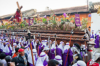 Antigua, Guatemala.  Cucuruchos Carrying  a Float (Anda) in a Religious Procession during Holy Week, La Semana Santa.