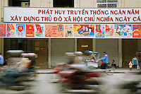 """Vietnam. Hanoi. Rush hour traffic. Scooters and bicycles on the road. Mother and child on the sidewalk. Flags of the Vietnamese Communist Party. Alphabet and writings in vietnamese language: """" Long life to the Communist Party. 04.04.09 © 2009 Didier Ruef"""