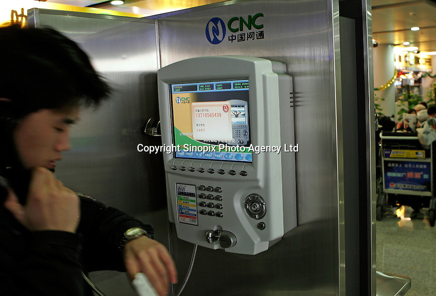 A man uses a CNC public video phone at the Beijing International Airport, China..